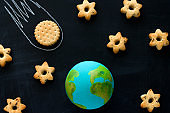 top view  handmade model  of Earth planet, cookie meteorite   and cookies in the shape of stars on the chalkboard