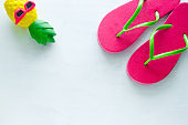 pink beach flip flops  and squishy toy pineapple in sunglasses on white  background