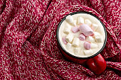 warming drink with marshmallows on a red knitted sweater background