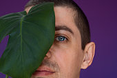 young man  holding tropical monstera leaf on violet background