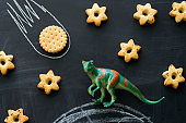 plastic dinosaur and cookies on the chalkboard, play and learning with the children