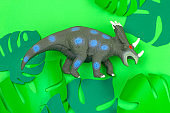 dinosaur toy on green background with green paper cut tropical leaves