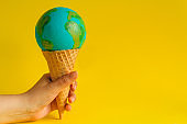 hand holds waffle cone with Earth model