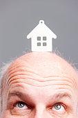 Senior balding man looking up at a model house