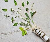 Ayurvedic herbal salt in glass jar. Sea salt with aromatic herb - rosemary, oregano, sage, marjoram, basil, thyme, mint, bay leaf. Copy space