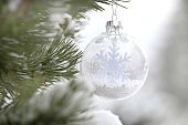 Christmas tree decor. Winter holidays.Transparent ball with a snowflake on a branch of spruce on a blurry light background