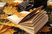 Writing Concept.Autumn Books. typewriter and books with yellow maple leaves on the lawn.Reading books about autumn