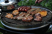 Meat and sausages are fried on the grill