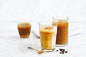 Iced coffee with cream and vanilla in various glasses on white background. Summer cocktail or dessert
