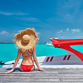 Woman in bikini sitting on jetty with boat