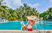 Toddler boy in resort swimming pool with mother