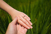 Romantic marriage proposal . close up hands of couple in love holding together , the woman with engagement ring on her finger isolated on green field background