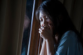 dramatic indoors portrait of young sad and depressed Asian Chinese woman crying desperate broken heart suffering depression and anxiety in dark light at home curtains window in sadness concept