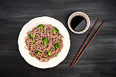A plate of soba, buckwheat noodles with green vegetables, with chopsticks and soy sauce, shot from the top on a black background with copy space