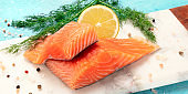 Slices of salmon with lemon and dill, close-up panoramic shot with salt and pepper, cooking fish, on a blue background