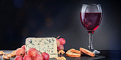 A panorama of gorgonzola cheese with red wine on a dark background with copy space
