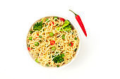A bowl of soba noodles with vegetables and a red pepper, shot from above on a white background with a place for text