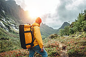 Brave tourist wearing yellow jacket with travel backpack hiking in mountains outdoor journey. Active traveler lifestyle wanderlust