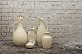 Pottery, vase, jug of white clay on a gray stone background. Pottery mock-up made from white clay on a gray background.