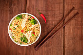 Soba noodles with vegetables and chicken meat, shot from the top on a dark rustic wooden background with chopsticks