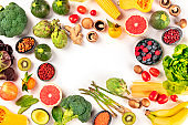 Vegan food. Healthy diet concept. Fruits, vegetables, pasta, nuts, legumes, mushrooms, shot from the top on a white background, forming a frame with a place for text. A flat lay composition