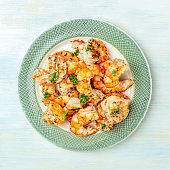 Fired shrimps with fresh parsley leaves, square overhead shot