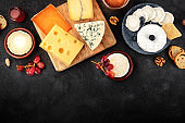 Cheese assortment with copy space, a flat lay overhead shot on a dark background with a place for text