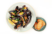 Marinara mussels, shot from the top on a white background with toasted bread and copy space