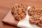 Freshly baked golden brown chocolate chip cookies on a dark rustic wooden background with copy space