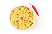 Soba noodles on a white background with red peppers and green onions, overhead shot with copy space