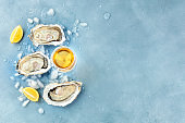 Fresh raw oysters, shot from the top on ice with a glass of white wine, lemon slices, and a place for text