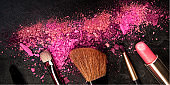 A panorama of make-up brushes, lipstick, and crushed cosmetics, shot from the top on a black background with a place for logo, a beauty design template for a makeup banner