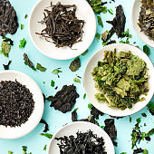 Various dry seaweed, sea vegetables, square overhead shot on a teal background