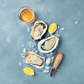 Fresh raw oysters, square top shot on ice with a glass of white wine, lemon slices, and a shucking knife