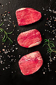 Raw beef steaks with salt, pepper and rosemary, top shot on a black background