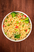 Soba noodles with vegetables, shot from above on a dark rustic wooden background with copyspace