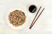 A plate of buckwheat noodles with green vegetables, with chopsticks and soy sauce, shot from the top on a light background with copy space