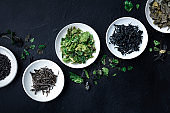 Various dry seaweed, sea vegetables, shot from the top on a black background with a place for text