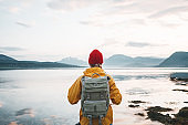 Alone traveler wearing yellow raincoat and backpack looking at fantastic fjord and mountain landscape. Lifestyle outdoor adventure, scandinavian wanderlust