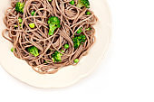A closeup of a plate of cooked soba, buckwheat noodles with green vegetables, shot from above on a white background with a place for text