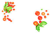 Fresh basil leaves and cherry tomatoes, shot from the top on a white background, forming a frame for copy space