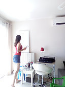 Beautiful girl in shorts and red t-shirt painting a table in a house with inspiration and talent