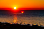 The sun rises (sunrise) over the sea, early morning