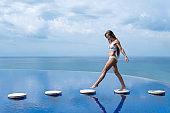 sexy girl. beautiful woman. model lady bikini underwear sit edge of water swim pool on the roof of luxury resort hotel nice sea scenery long shot