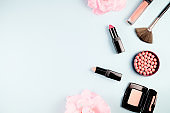 Beauty background makeup cosmetic product,with green leaf and pink rose blossom on purple spring background. woman mother day concept. flatlay topview
