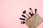 Makeup cosmetic with beauty bag on  pink background. lipstick, brush, eye shadow and accessories. woman fashion.