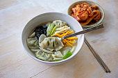 Korean food rice cake and Dumpling Soup, Tteok Mandu Guk with kimchi