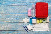 Top view first aid bag kid with medical supplies  on wood background.