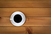 Cup of coffee on wood background, top view.