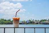Glass of cold espresso coffee on the iron balcony Background views of the river and the home.